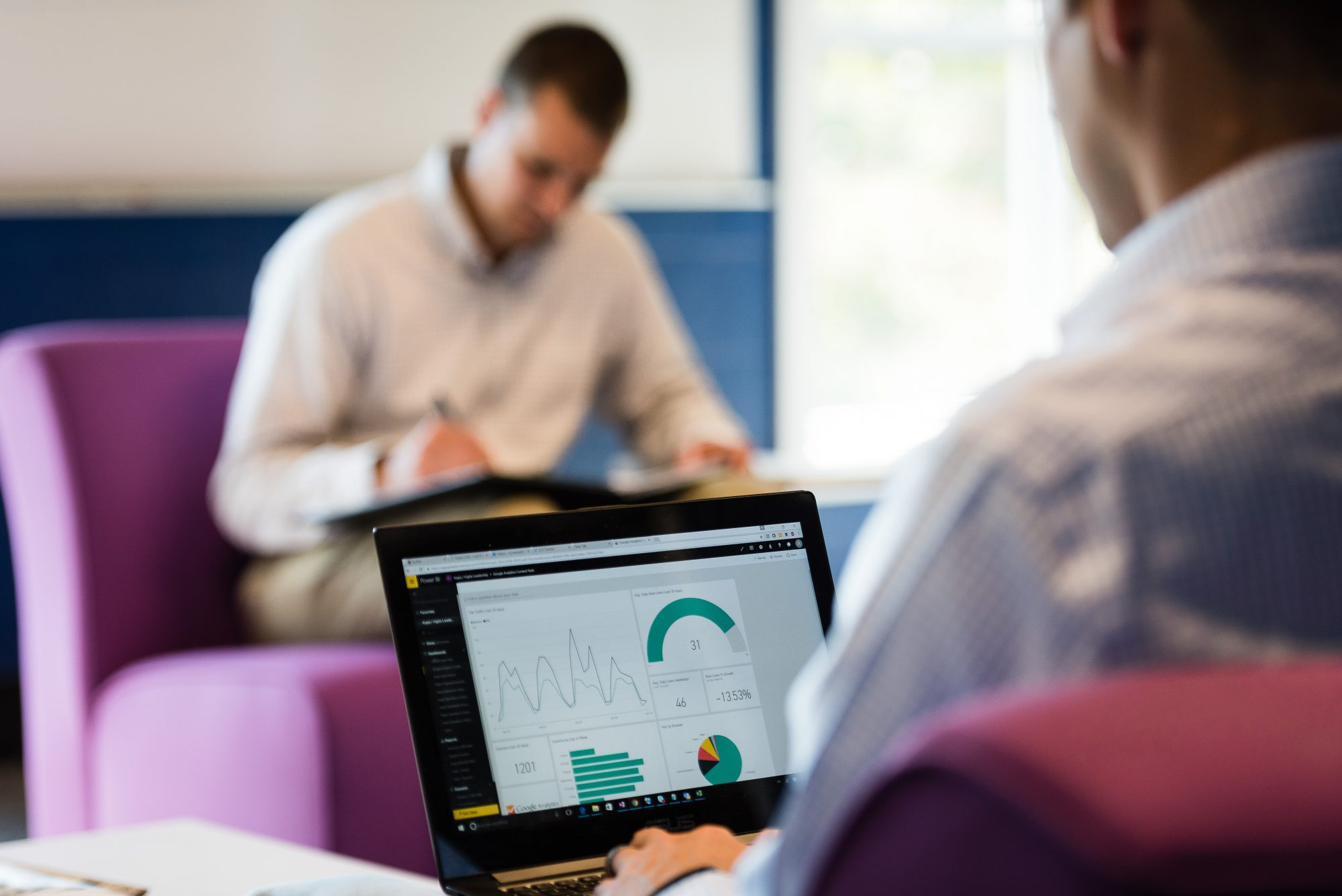 Man looking at laptop with business intelligence dashboard displayed