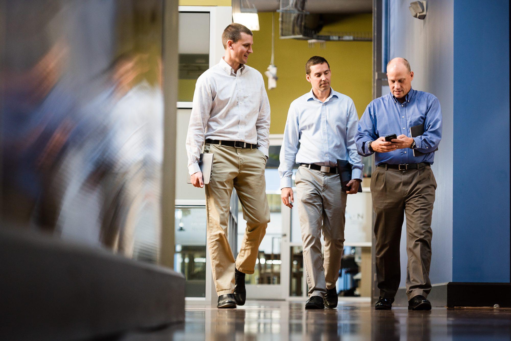 Three men walking down hallway looking at a phone