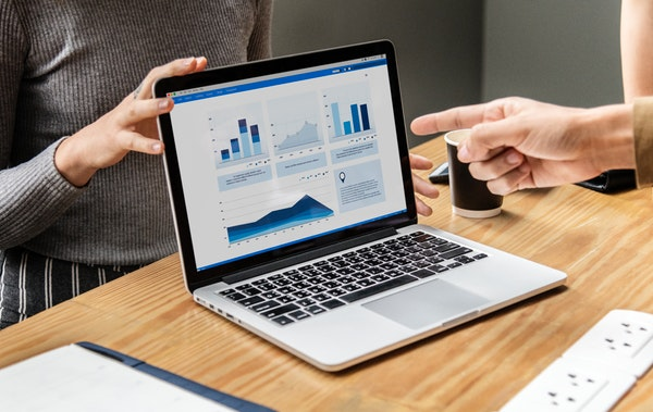 Finger pointing at laptop screen with infographics displayed