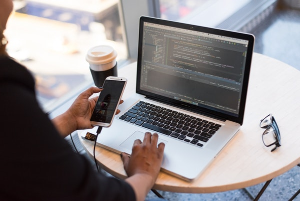 Woman holding phone and looking at macbook with code on screen