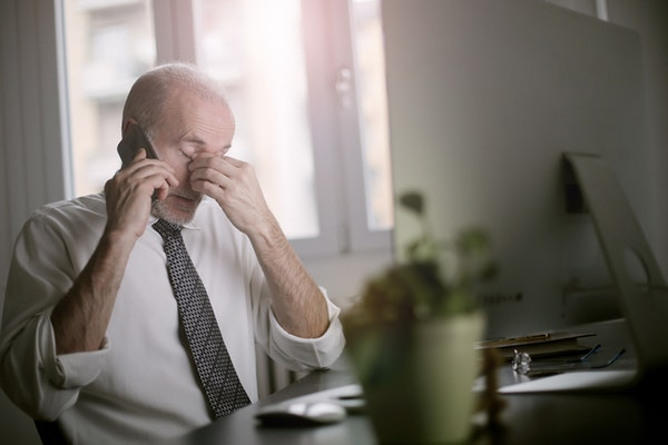 businessman rubbing eyes while talking on a smartphone