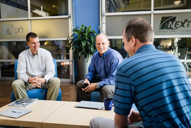 Three men smiling and talking at a desk