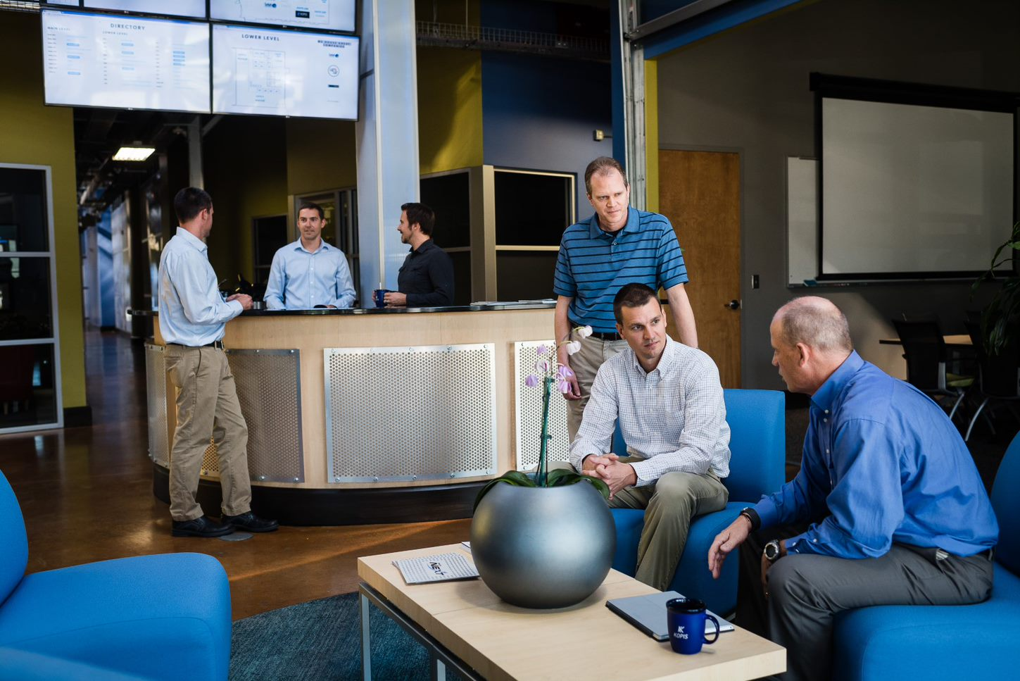 Group of guys talking in lobby of office